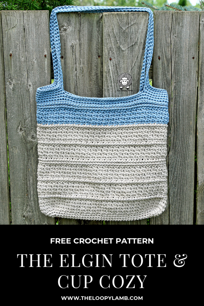 The Elgin Tote Bag, a grey bag with a blue stripe at the top hanging on a fence.