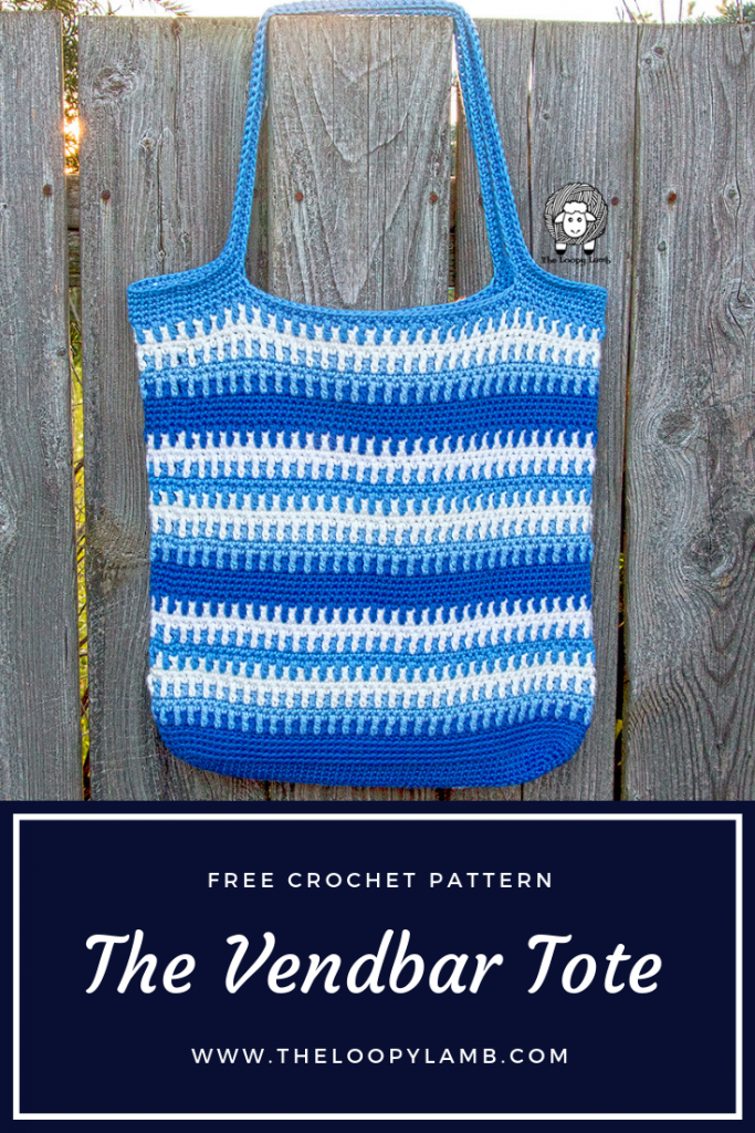 The Vendbar Tote Bag, made with this crochet tote bag free pattern, hanging on a fence, comprised of stripes of blue and white.