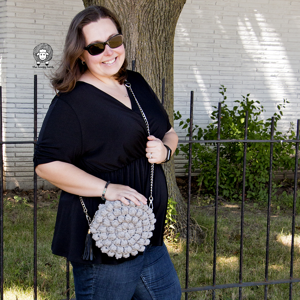 Woman wearing a gray bobblelicious crochet bag made with this crochet pattern