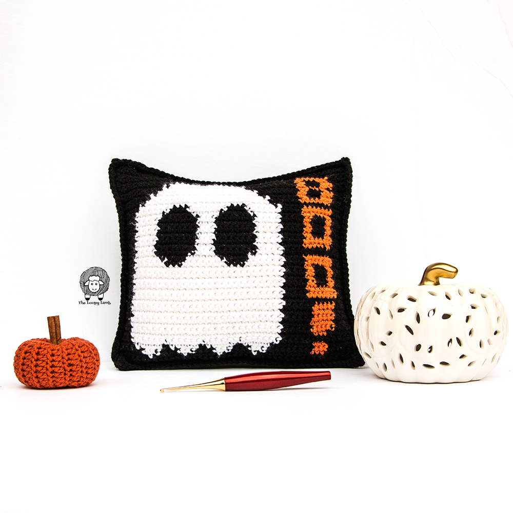 The Mad About Boo Pillow is a Black Crochet Halloween Pillow with a White Ghost and the word Boo on it in orange.
