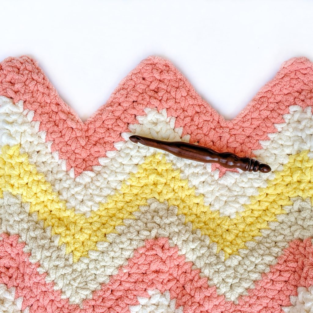 Crochet Chevron Blanket made with Bernat Blanket Yarn with a handmade wooden crochet hook on top.