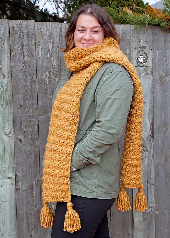Woman looking off-screen wearing the Heather Super Scarf in mustard