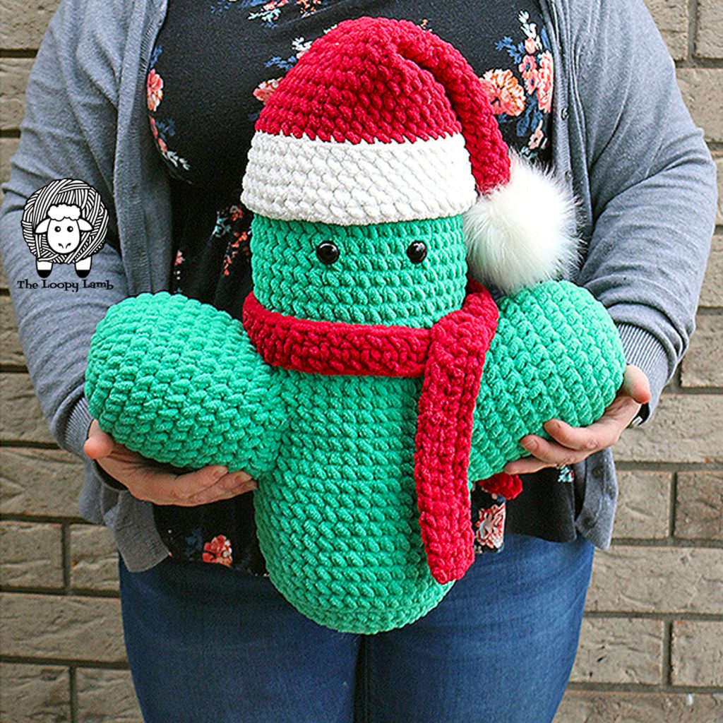 jumbo amigurumi cactus cuddler being held in front of a woman. free  crochet christmas decoration pattern