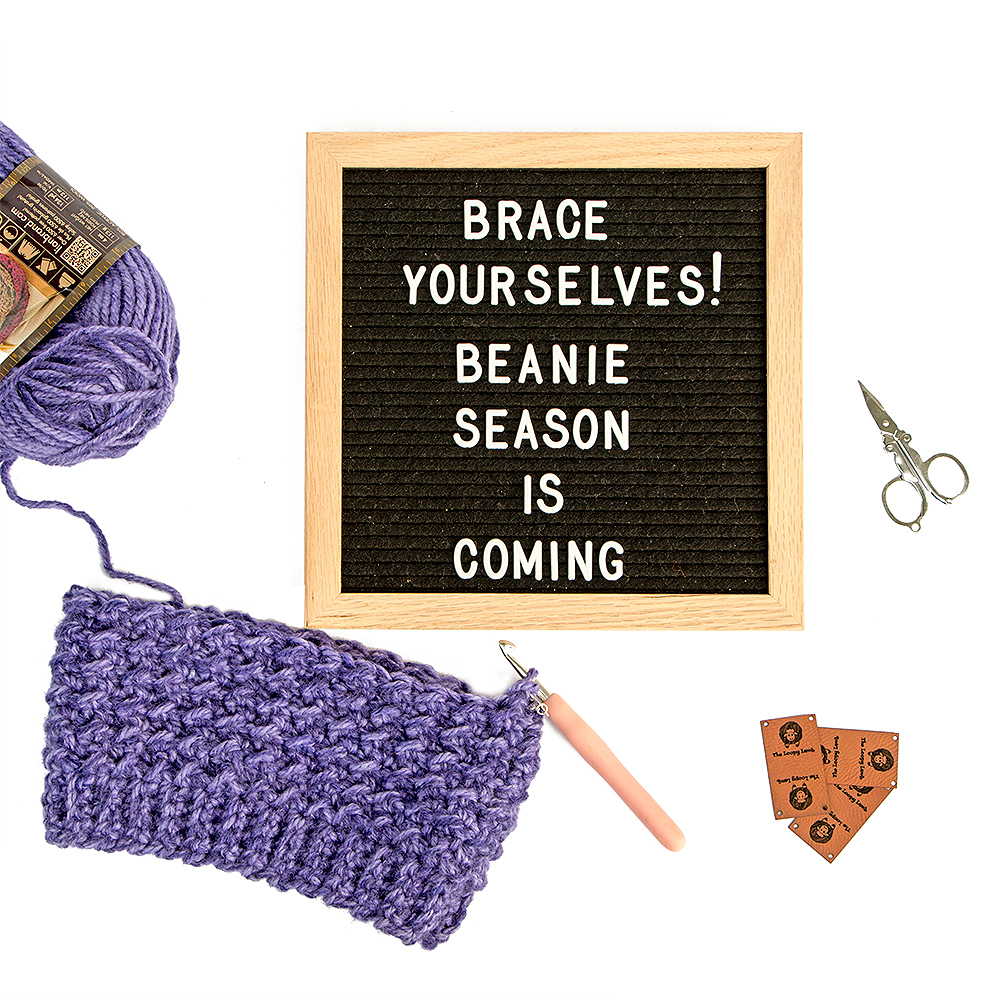 Flatlay image of a letter board that says Brace Yourself. Beanie Season is coming.  A work in progress crochet hat project and personalized faux leather tags from Unwrapped yarn.  Christmas gift ideas for crocheters