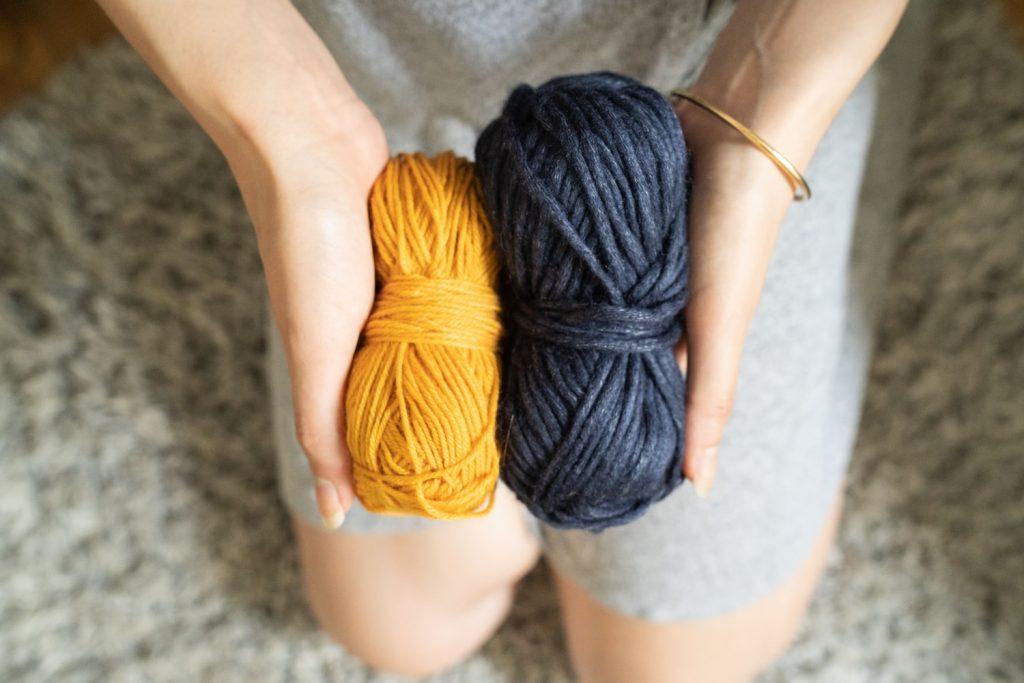 Kneeling woman holding two skeins of yarn in front of her.