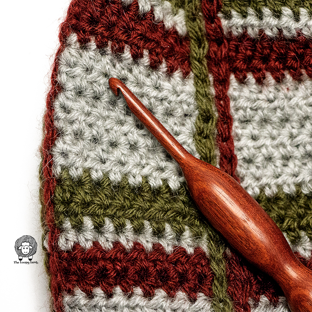 Close up of stitches on the Crochet Tartan Beanie with a wooden crochet hook on top