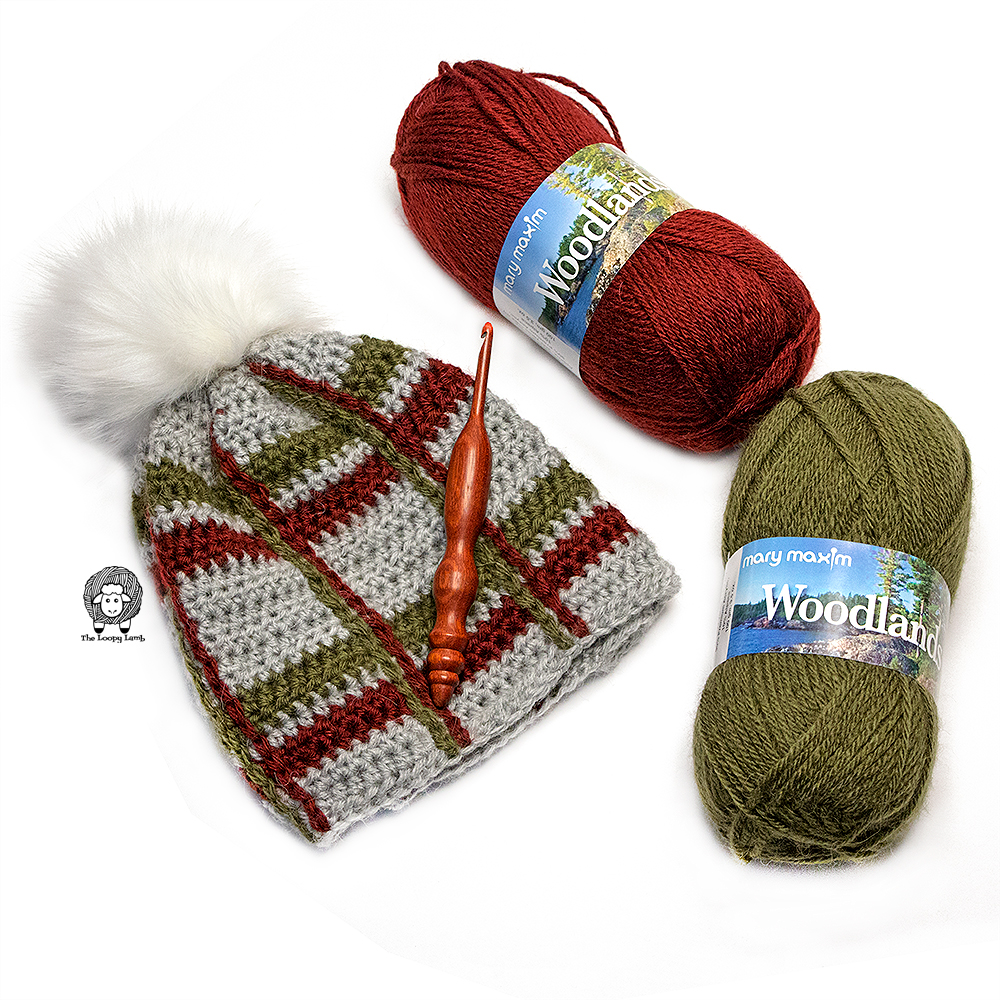 Crochet Tartan Beanie folded and lain flat with a wooden crochet hook on top. Two balls of Mary Maxim Woodlands yarn next to it.