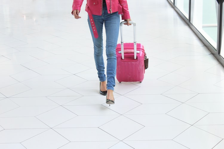 woman carrying a small pink suitcase