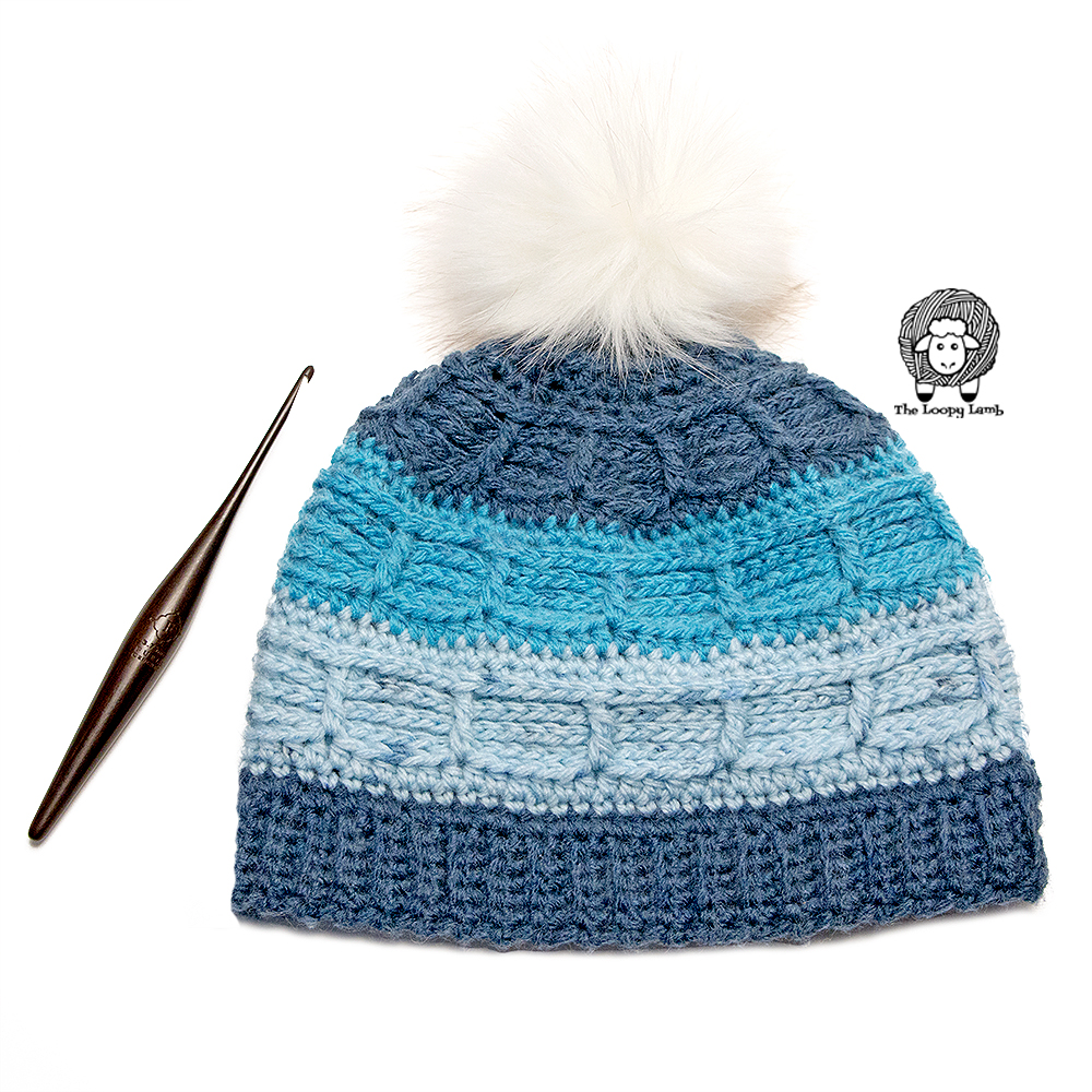 Juneau Blues Beanie laid flat next to a furls crochet hook.