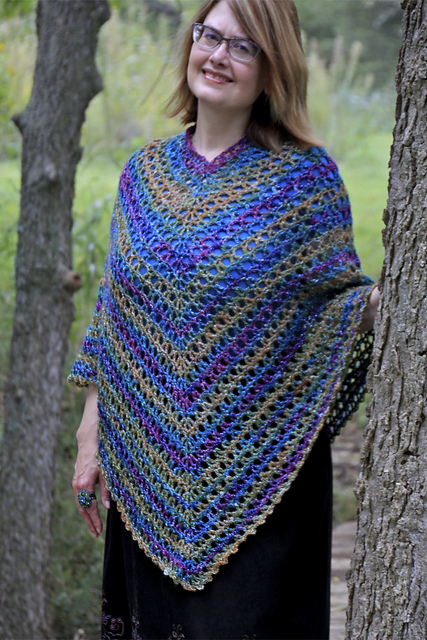 Woman wearing lacy, striped poncho made with a free crochet poncho pattern.