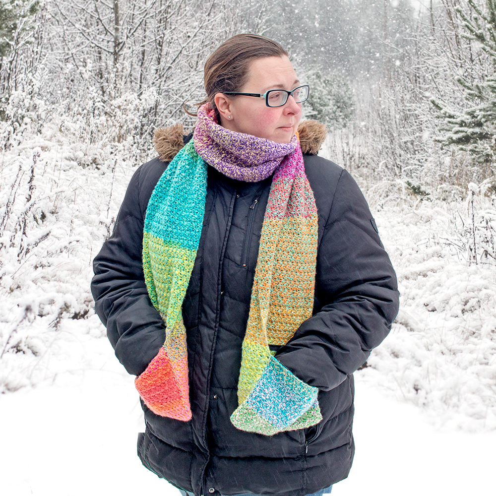 Woman wearing a colourful crochet scarf in a snowy forest made with this free crochet scarf pattern