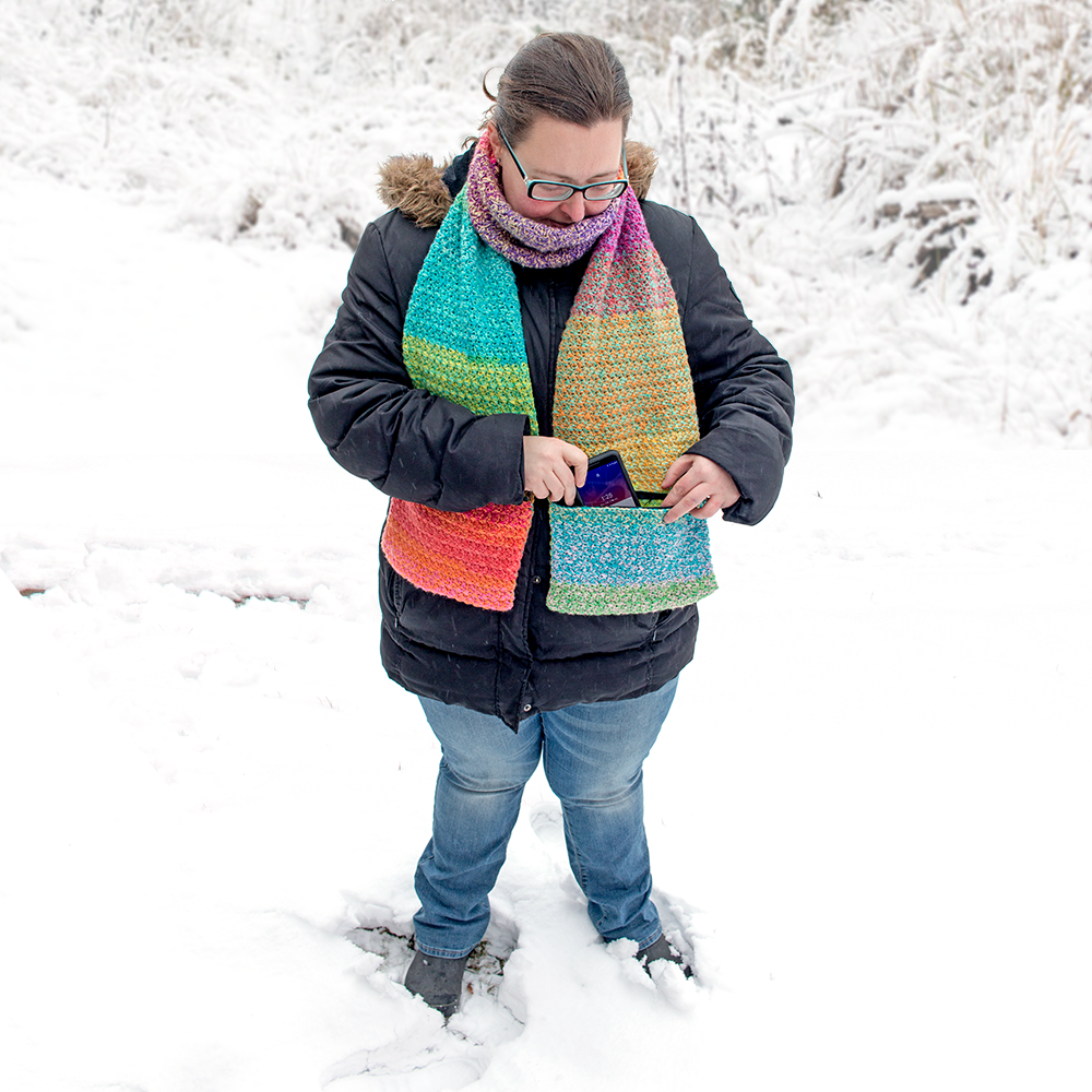 Woman wearing a crochet scarf and taking her phone out of the pocket. Scarf was made with this easy crochet scarf pattern.