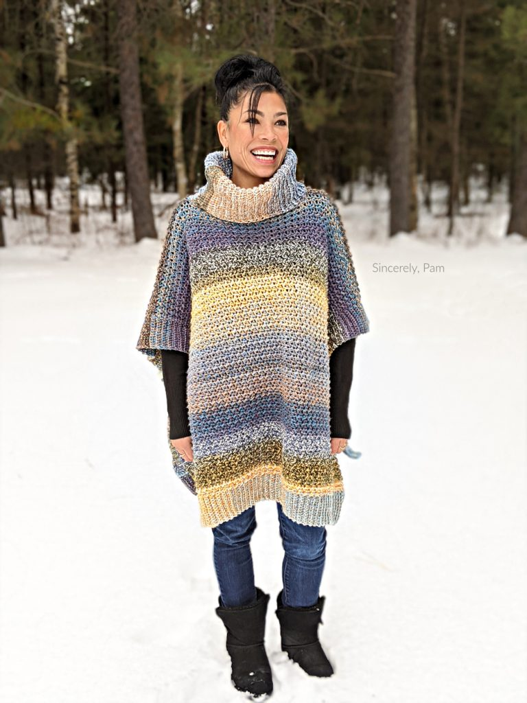 Smiling woman wearing the lucky penny crochet poncho.