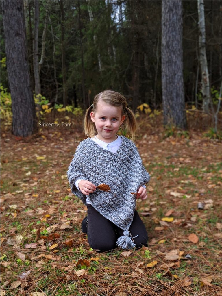 Child kneeling on the ground wearing the ragged falls crochet poncho