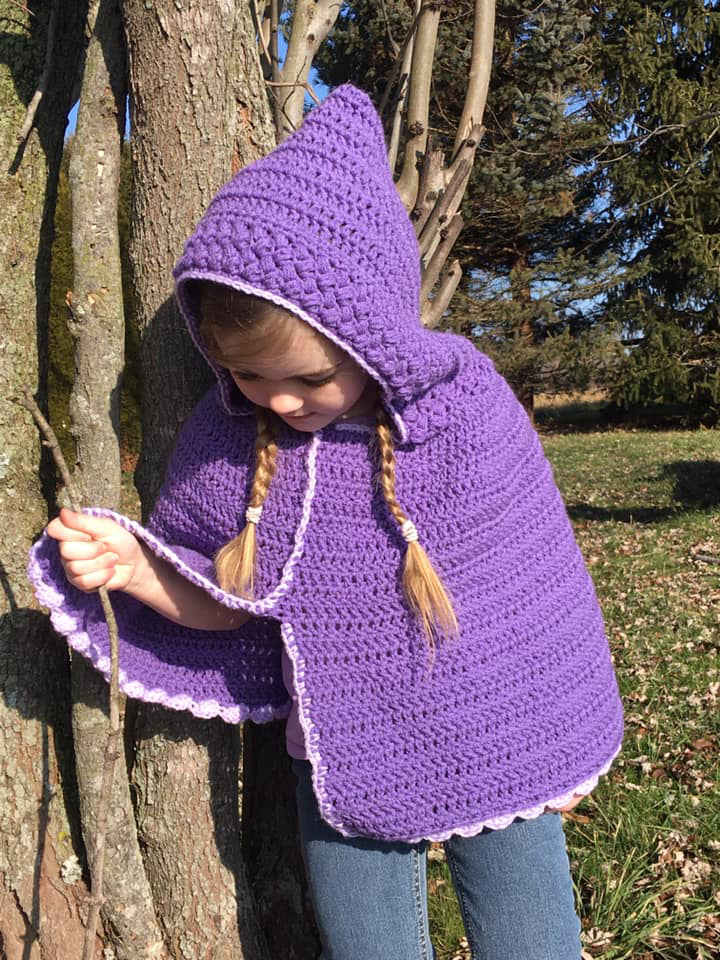 Child wearing a hooded poncho made with a free crochet poncho pattern