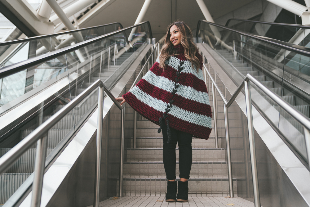 Woman wearing a striped poncho while walking down stairs