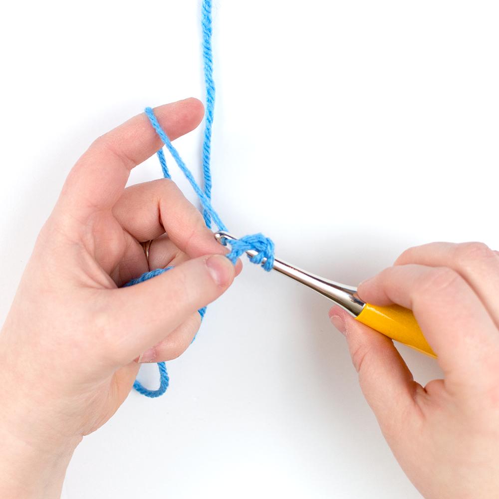 Step 3 of the crochet stitch tutorial using blue yarn