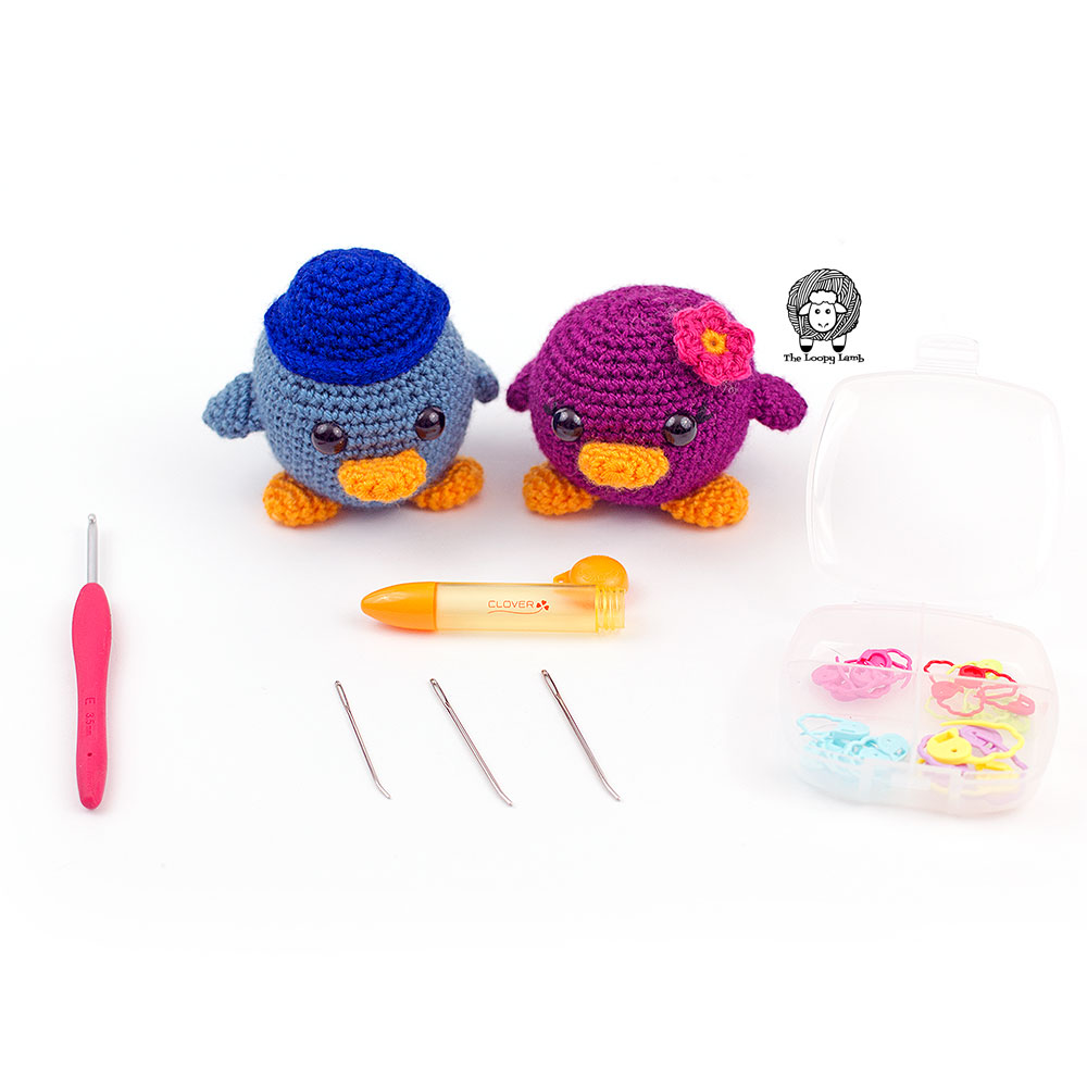 Two amigurumi birds standing in front of clover usa products used in the free crochet pattern