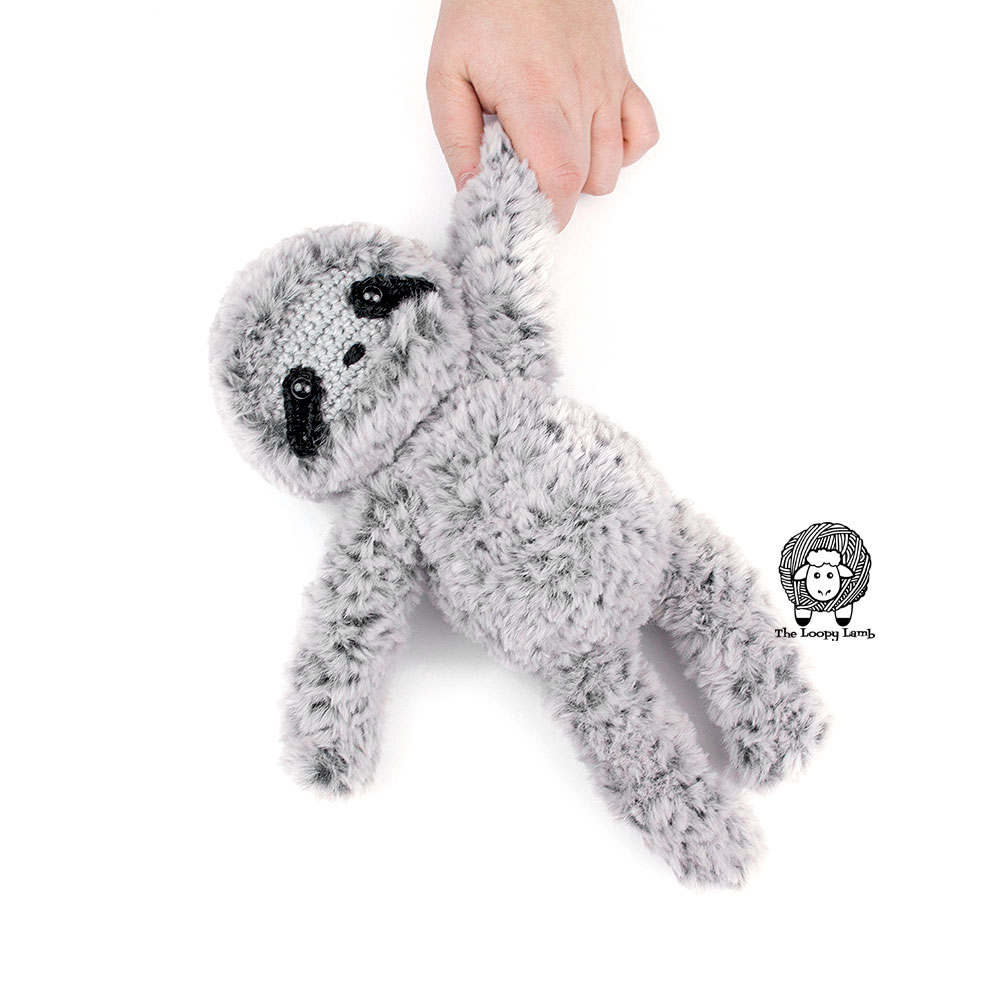 amigurumi sloth being held by the hand.