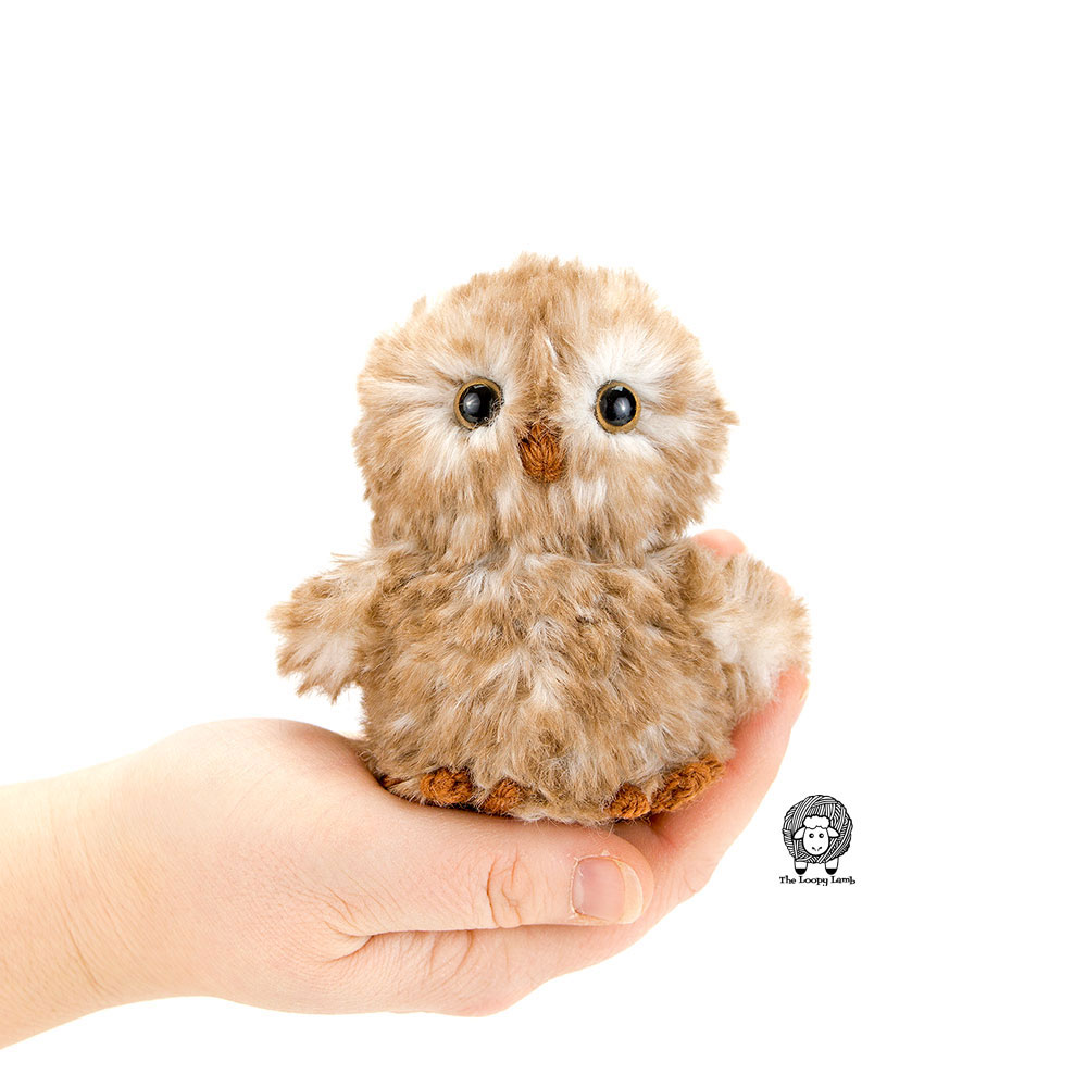Picture of an amigurumi owl that was made with this crochet owl free pattern sitting in the palm of a hand