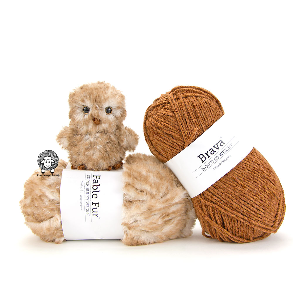Amigurumi Owl made with faux fur sitting on top of a ball of fable fur yarn