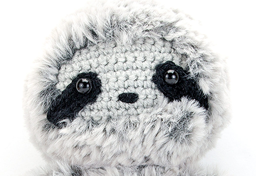 Close up image of the face of the crochet sloth made with this free crochet sloth pattern