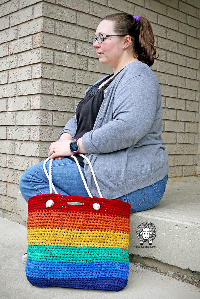 woman sitting next to the Rainbow Saver Tote made with this free crochet tote bag pattern.