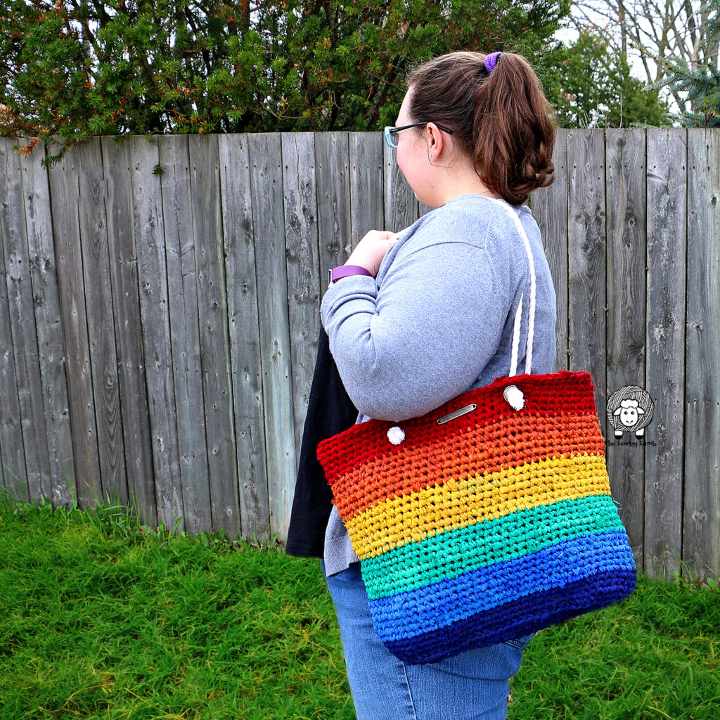 Girl holding the Rainbow Saver Tote bag made with this free crochet tote bag pattern.