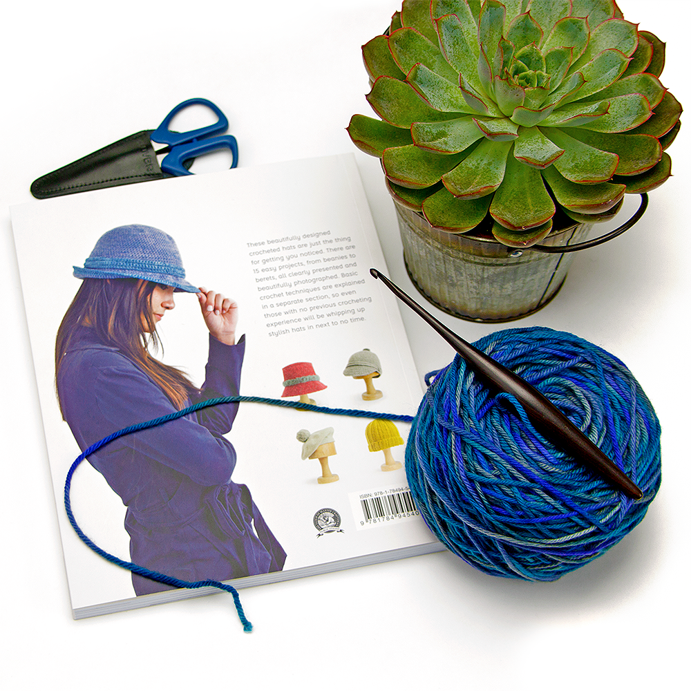 Back cover of the book Simple Crocheted Hats, a Furls Crochet Hook and some blue Knitcrate yarn