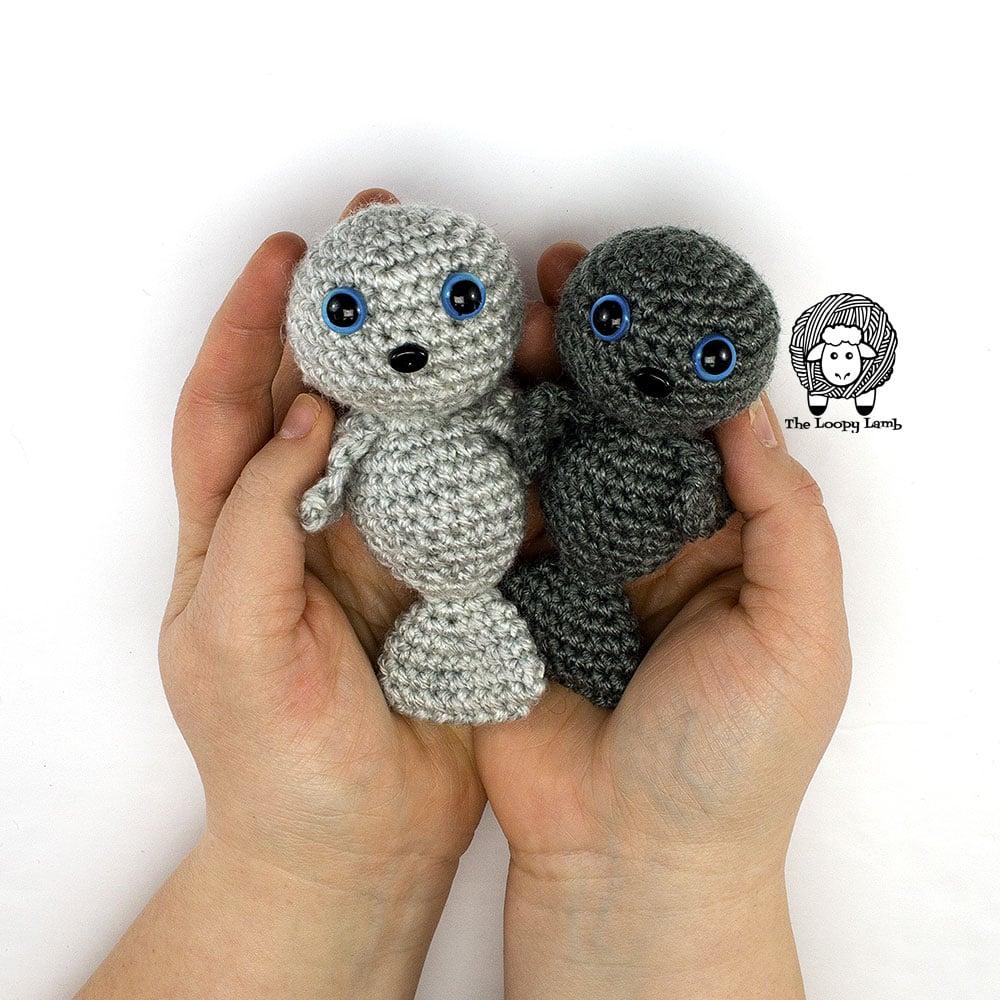 crochet baby seals held in someone's hands