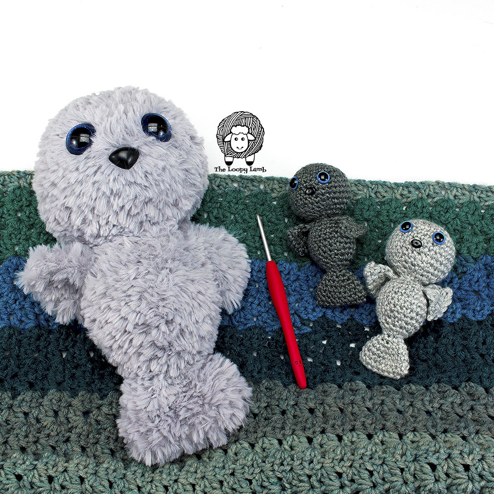 a large furry crochet seal and two baby amigurumi seals laying together on a blanket.