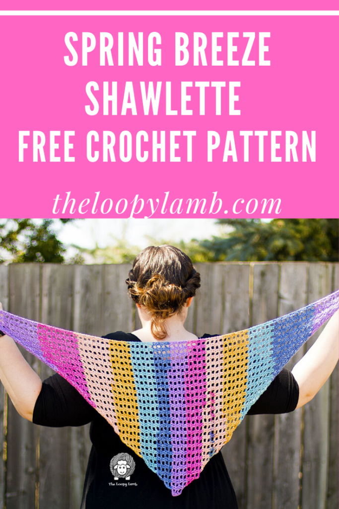 woman holding a colourful spring breeze shawlette behind her made with this crochet shawlette free pattern