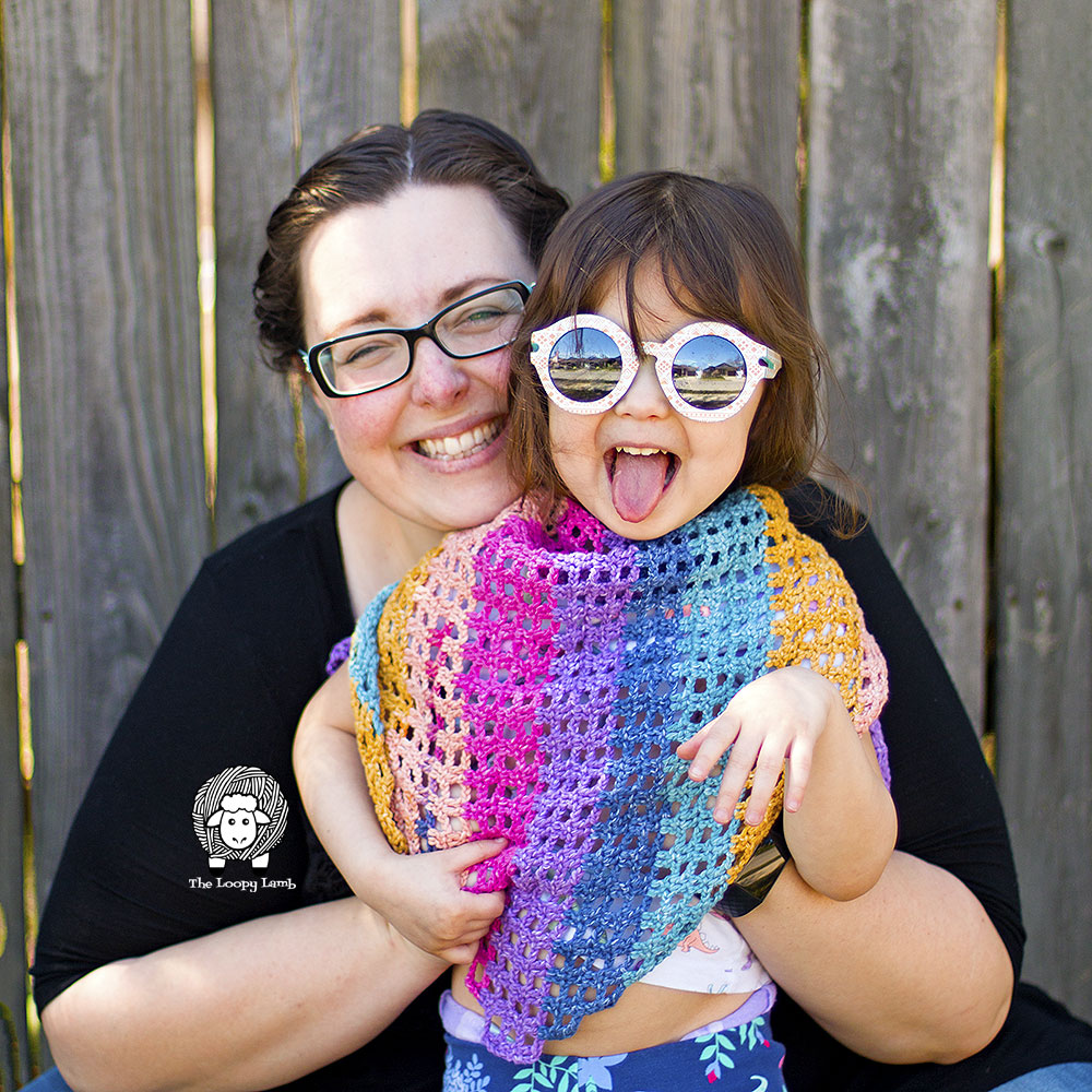 Smiling woman hugging a smiling child who is wearing a spring shawlette