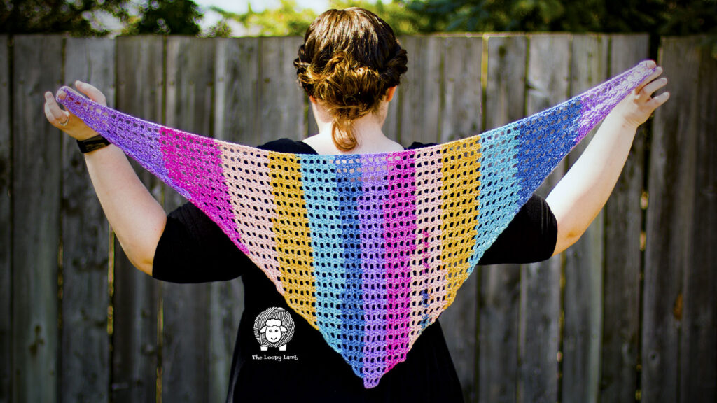 Woman holding a shawlette made with this crochet shawlette free pattern behind her back