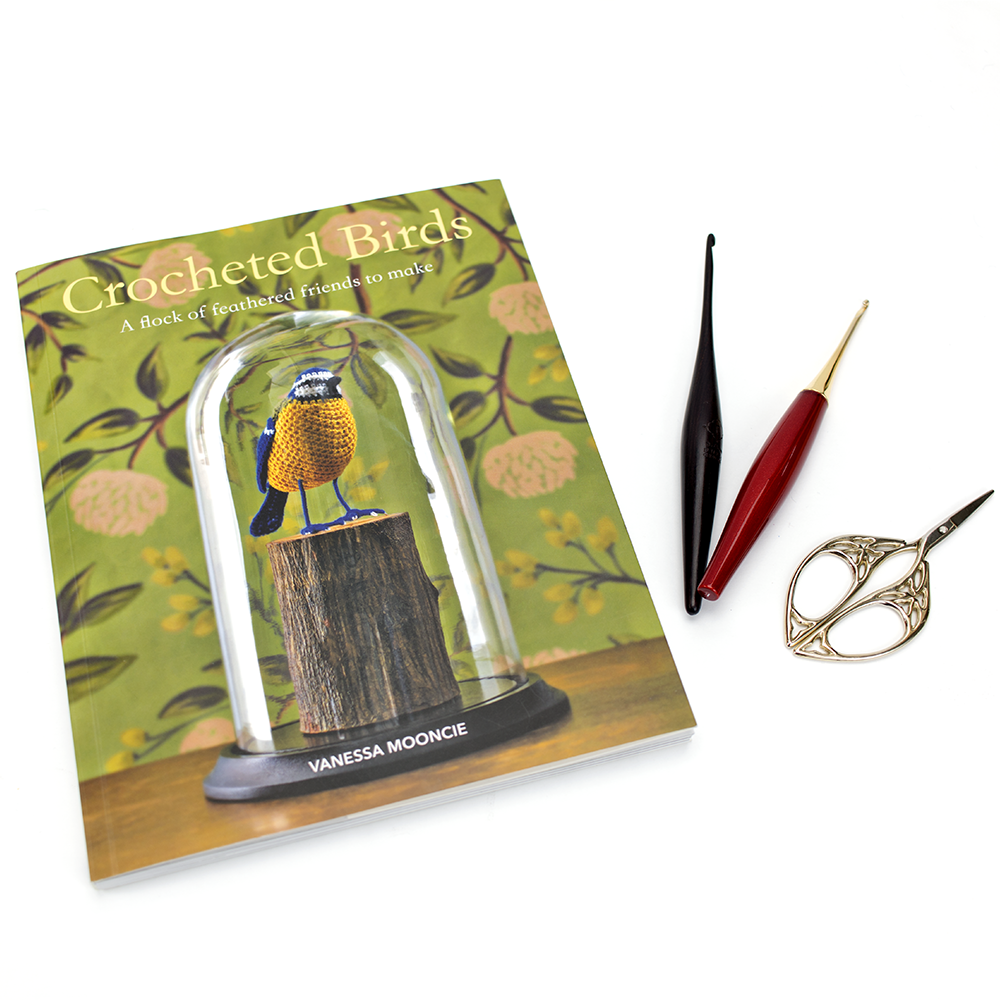 A copy of the Vanessa Mooncie Book Crocheted Birds with some furls crochet hooks and scissors