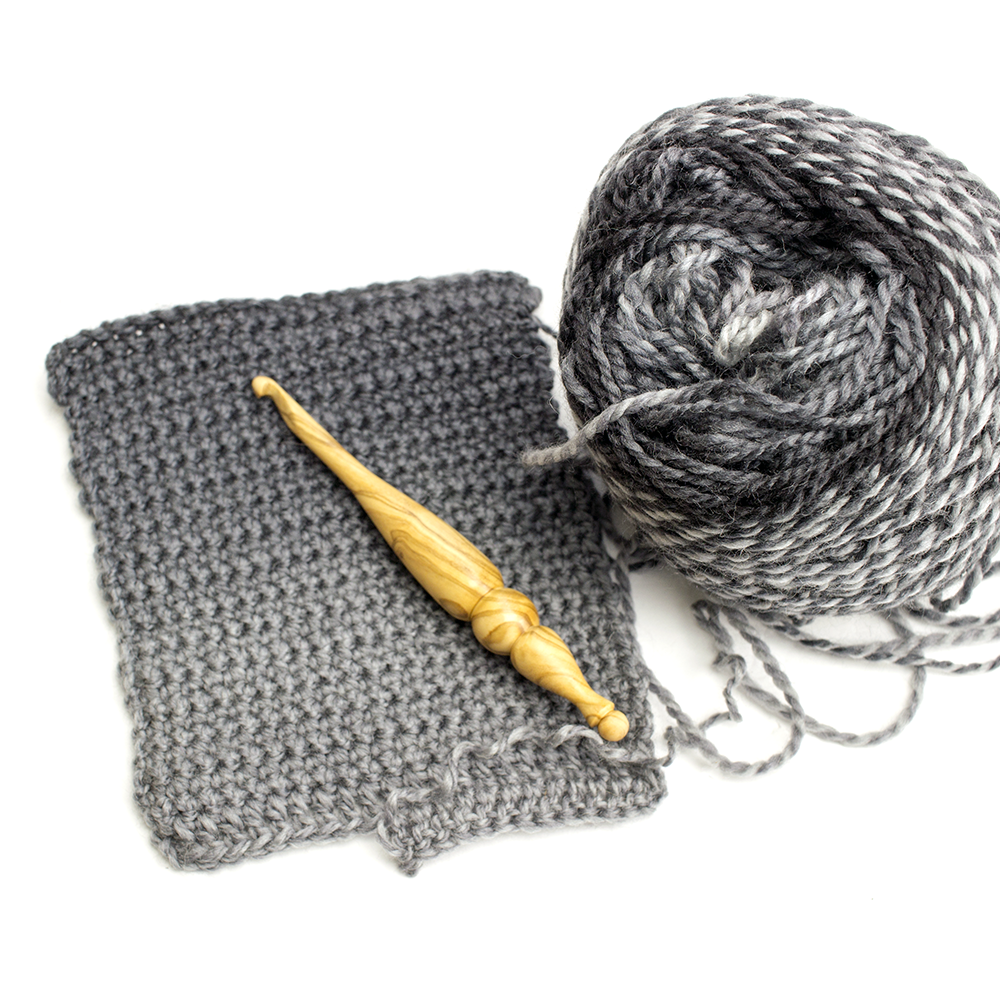 Crochet swatch with a wooden crochet hook on top, made with Chroma Twist Worsted Weight yarn in Wednesday.