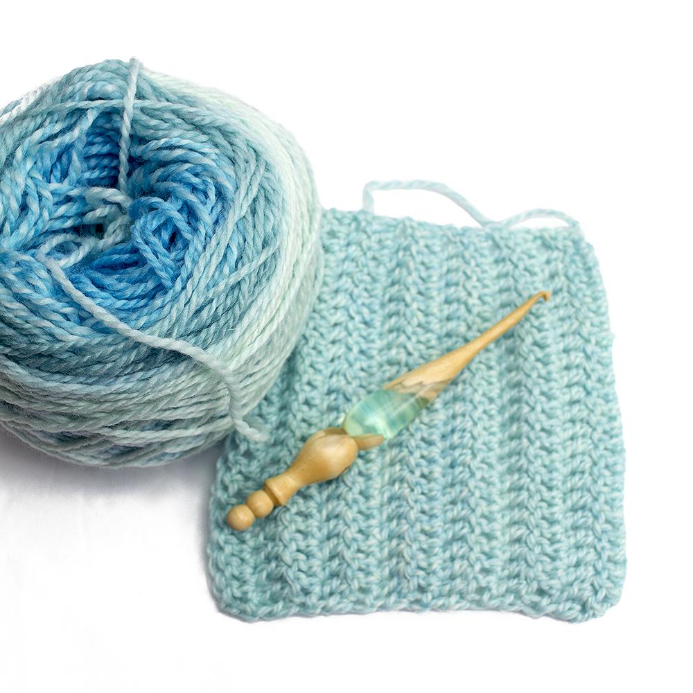 Furls crochet hook on top of a crochet swatch