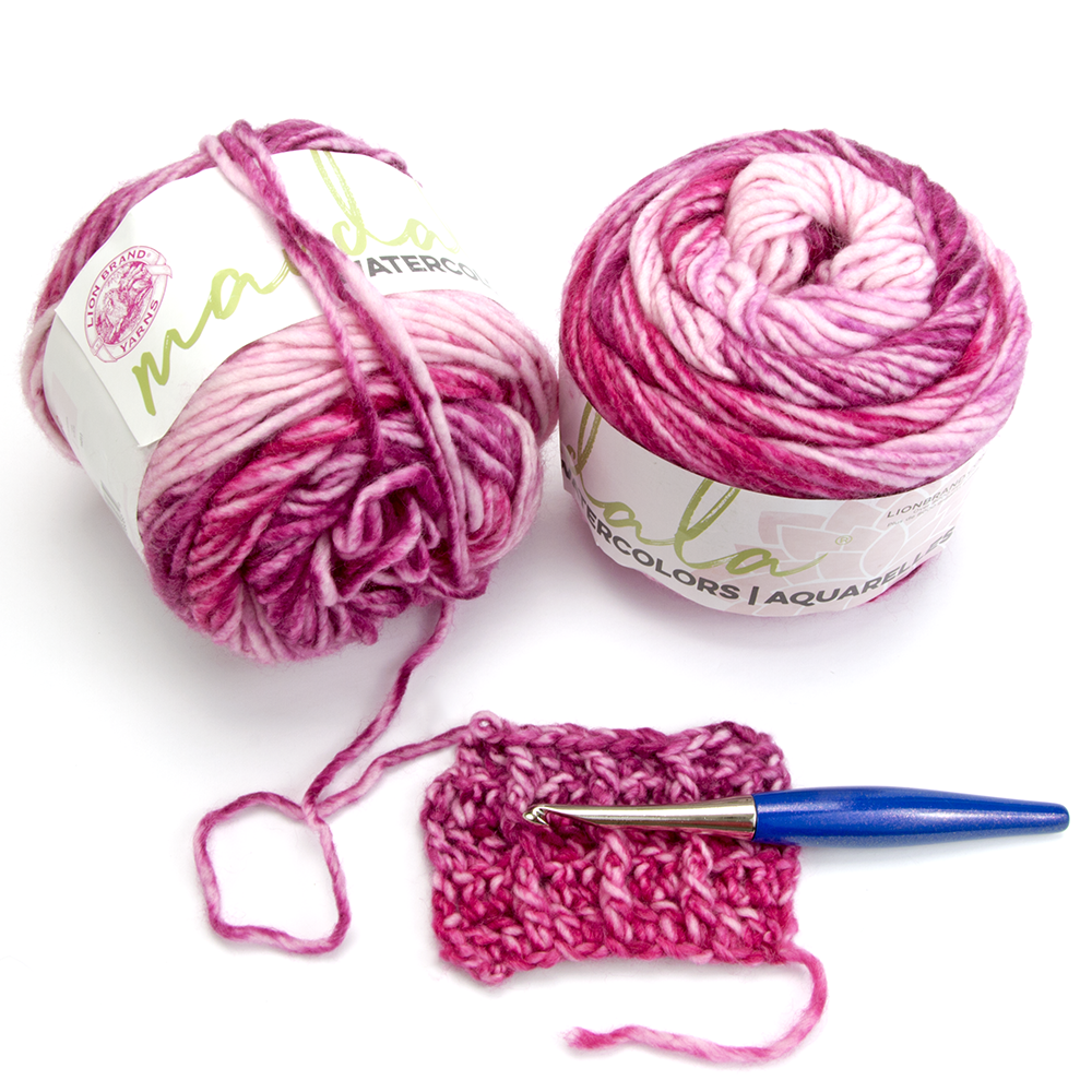 Two cakes of the yarn being reviewed in Teaberry with a furls crochet hook.