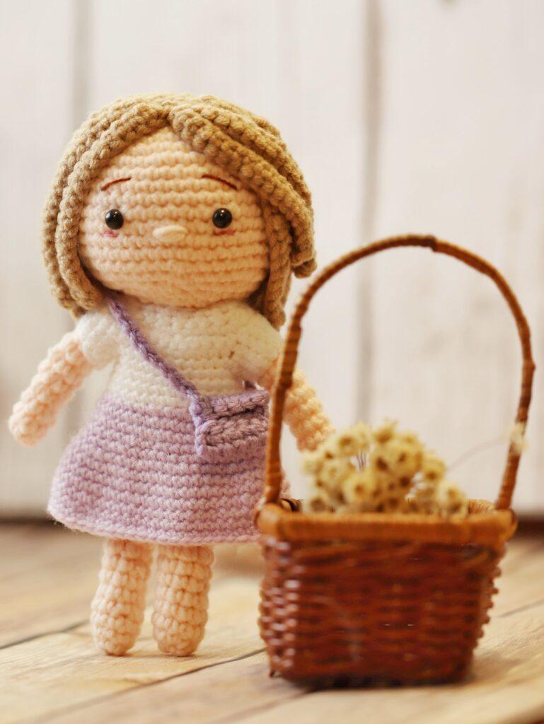 crochet doll wearing a purse next to a wicker basket