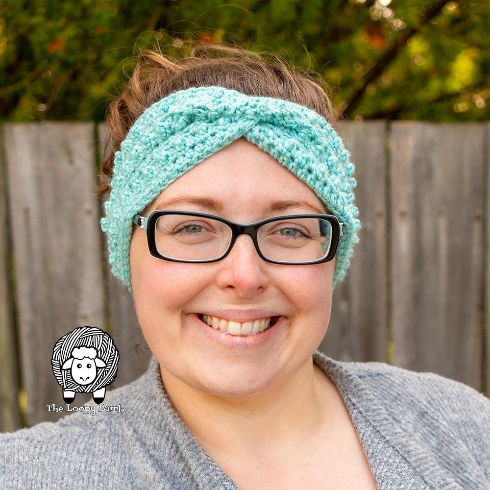 Smiling woman wearing a crochet ear warmer
