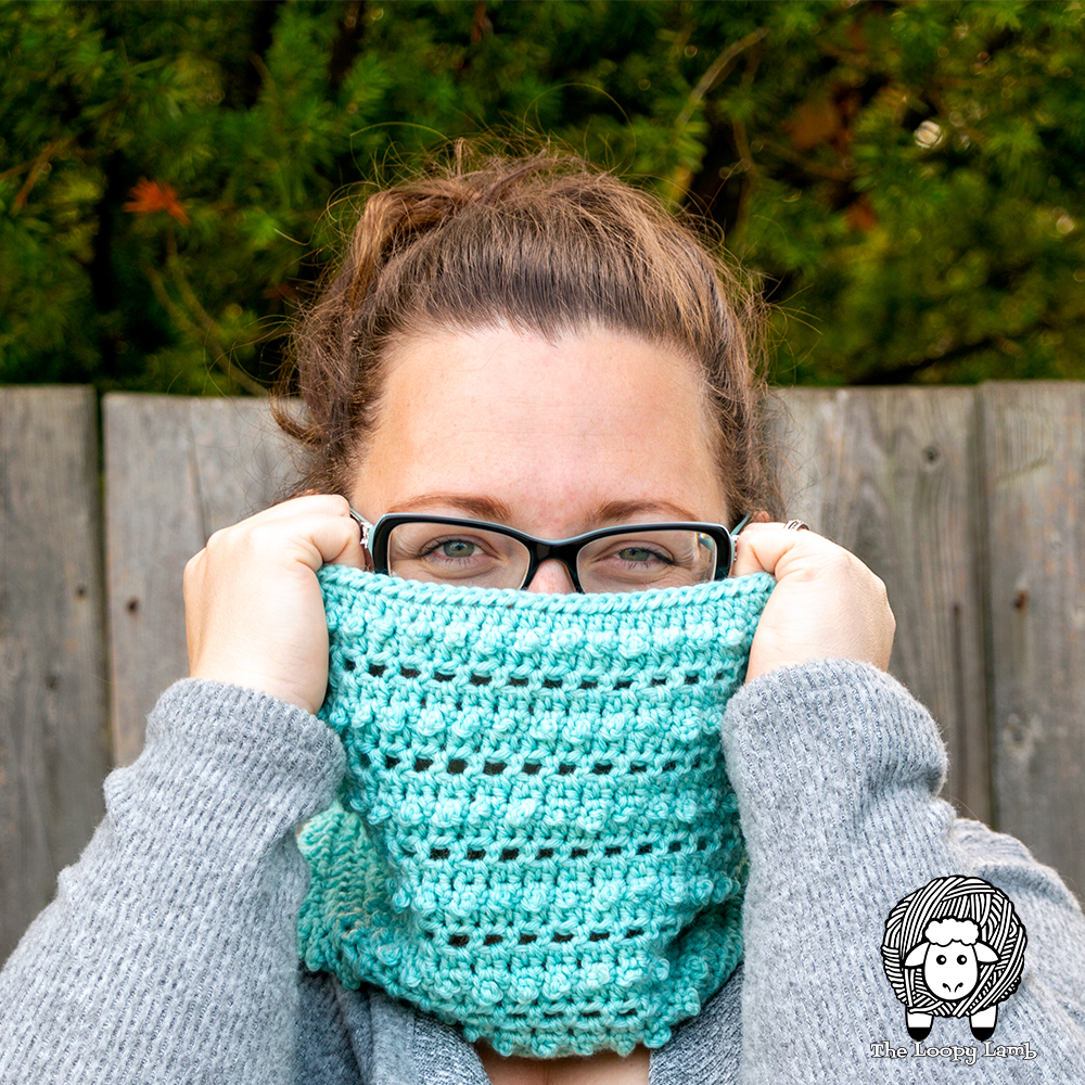Woman looking over the top of a crochet cowl with picot single crochet stitch bobbles