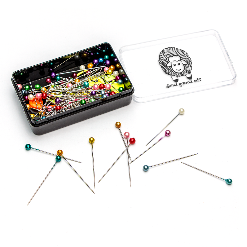 Sewing pins scattered next to a pin box