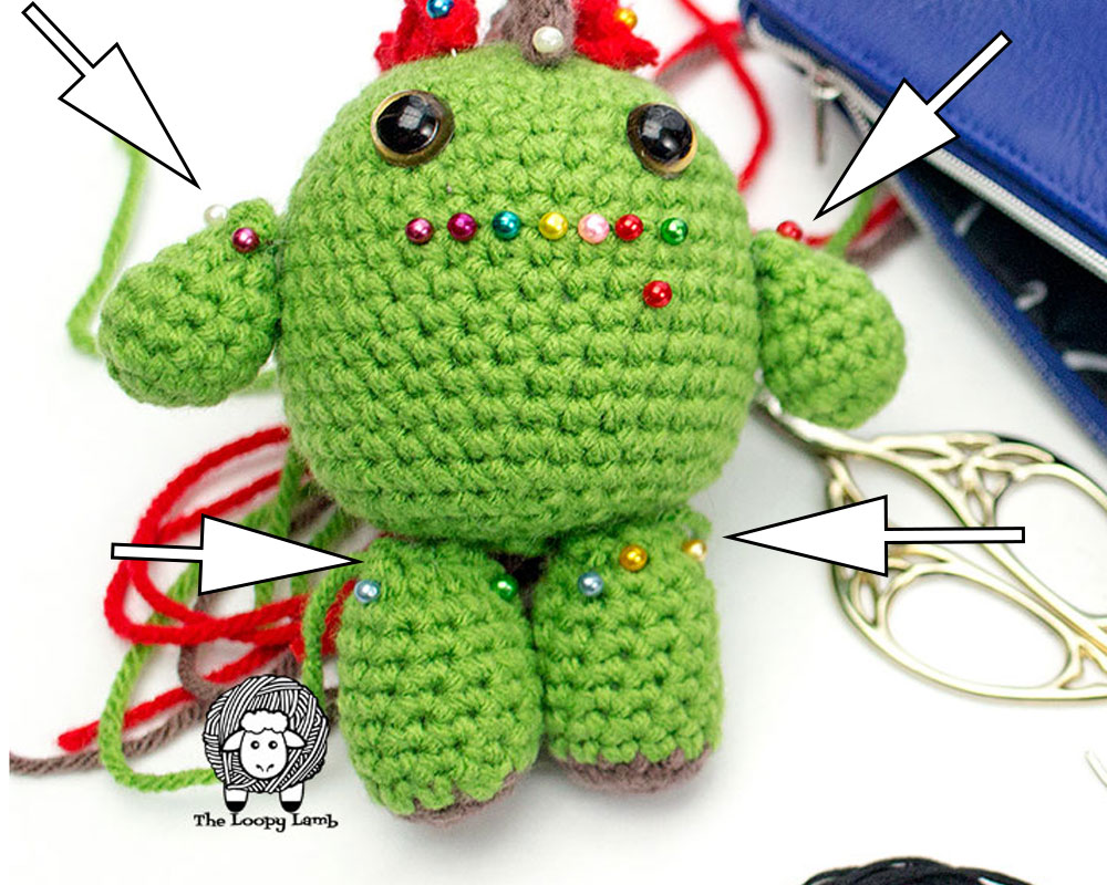 unfinished crochet toy being held together with sewing pins