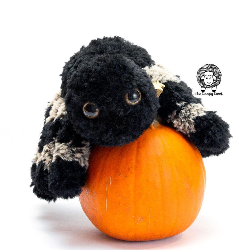 Furry crochet spider on top of a pumpkin