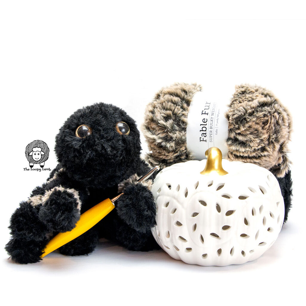 faux fur amigurumi spider holding a furls crochet hook