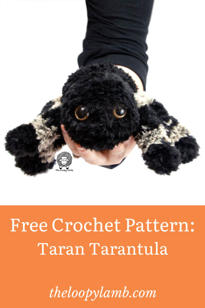 Hand holding a black and brown crochet tarantula made with this free crochet pattern