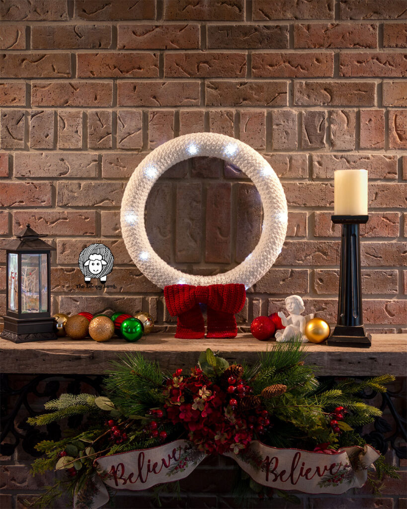 Christmas wreath lit up on a mantle