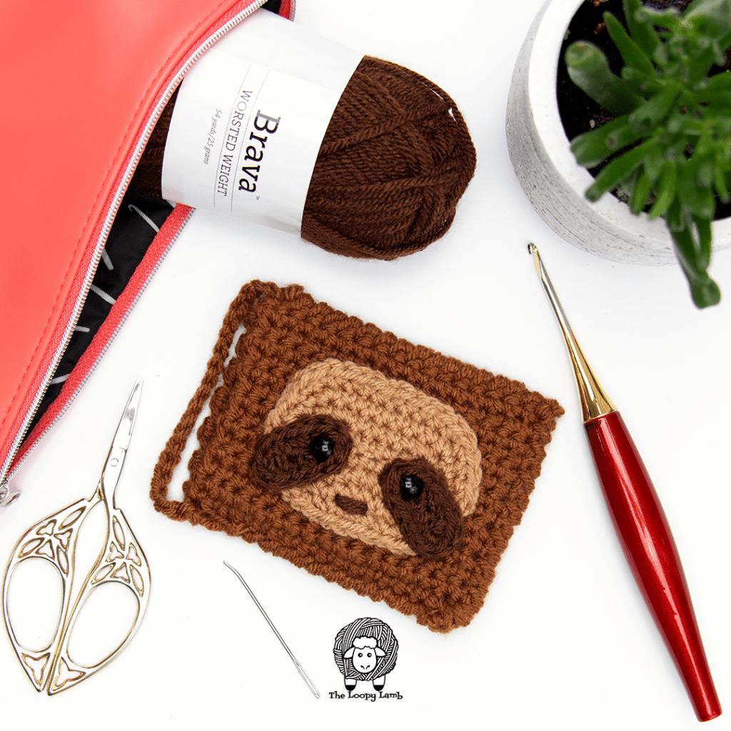 Sloth crochet gift card holder with a furls odyssey hook, scissors and brava yarn