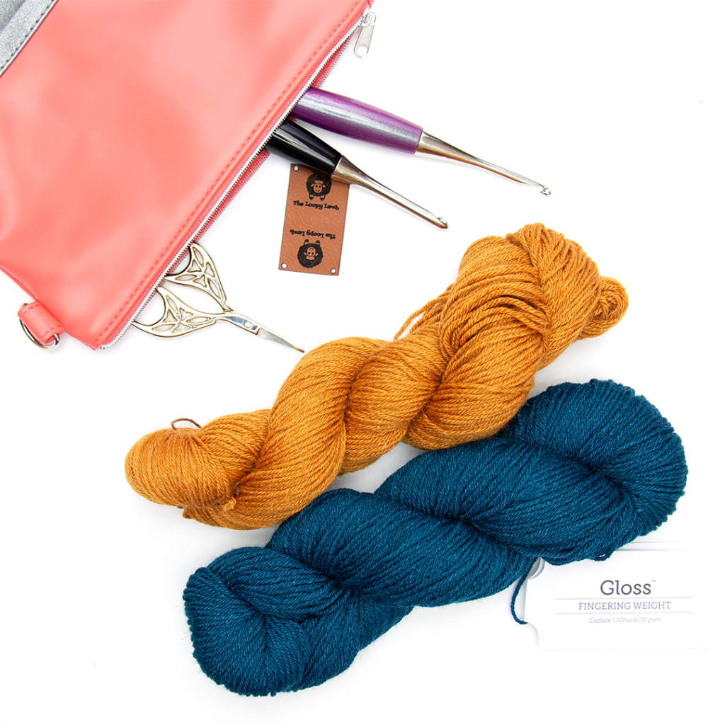 Two hanks of yarn with some crochet hooks and accessories
