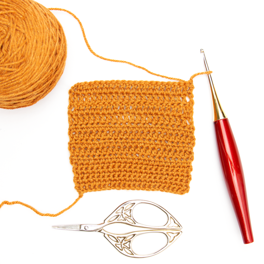 Gloss fingering yarn in harvest worked up in a crochet swatch